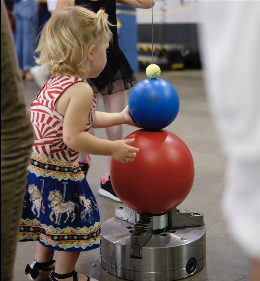 Child looking at Galilean Cannon at Carnegie Open House
